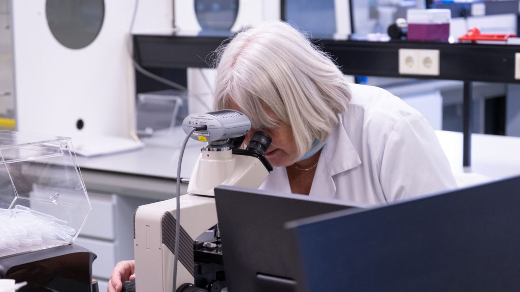 Female researcher with white hair looking into microscope